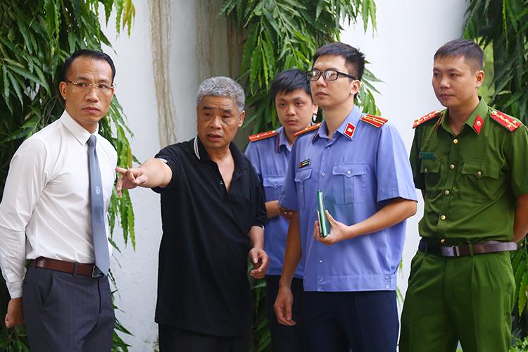 Ông Phiến (áo đen, thứ 2 từ trái sang) đang làm việc cùng cơ quan điều tra tại cổng trường Gateway. Ảnh: Phạm Dự.