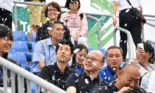 Các tình nguyện viên trải nghiệm tuyết giả ở Tokyo ngày 13/9. Ảnh: AFP.