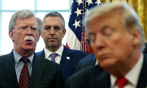 Tổng thống Trump lắng nghe ông Bolton phát biểu ở phòng Bầu dục, Nhà Trắng hồi tháng 2. Ảnh: Reuters.