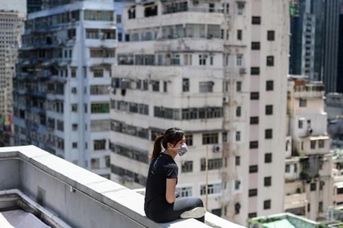 Jane, 24 tuổi, ngồi trên tầng thượng một tòa cao ốc ởHong Kong hôm 6/9, nhớ lại những lần cãi nhau với mẹ. Ảnh: AFP.