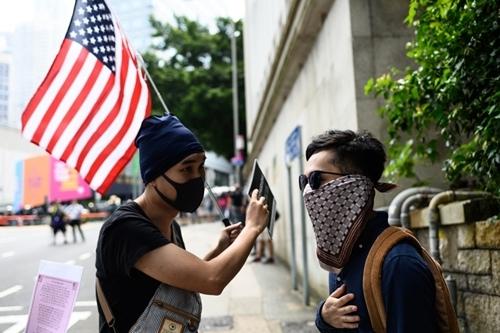 Chris (phải) tham gia một cuộc biểu tình và tuần hành gần lãnh sự quán Mỹ tại Hong Kong hôm 8/9. Ảnh: AFP.