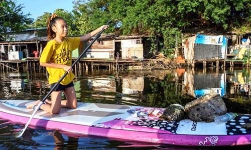 Lilly tự chèo thuyền gom rác trên một con kênh ô nhiễm ở Bangkok, Thái Lan. Ảnh: AFP.