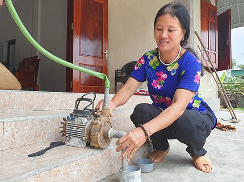 Máy bơm để lâu ngày hư hỏng, người dân phải thuê thợ về sửa để hút nước. Ảnh: Đức Hùng