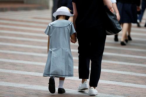 Một phụ nữ dẫn con gái đến trường ởKawasaki, Nhật Bản. Ảnh: Reuters