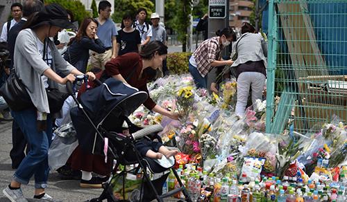 Người dân đặt hoa tại hiện trường một người đàn ông đâm 19 người, trong đó có nhiều trẻ em, tạiKawasaki hồi tháng 5. Ảnh: AFP