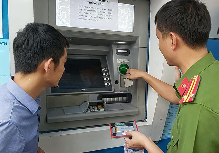 Cảnh sát thuật lại thủ đoạn của nhóm tội phạm gắn thiết bị điện tử vào cây ATM. Ảnh: Nguyễn Hải.