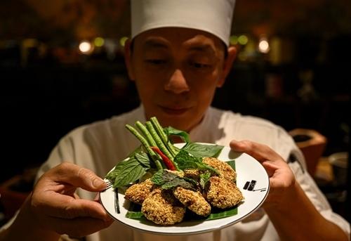 Đầu bếp khoe món chảlợn viên chay trong nhà hàng ở Bangkok hôm 4/9. Ảnh: AFP