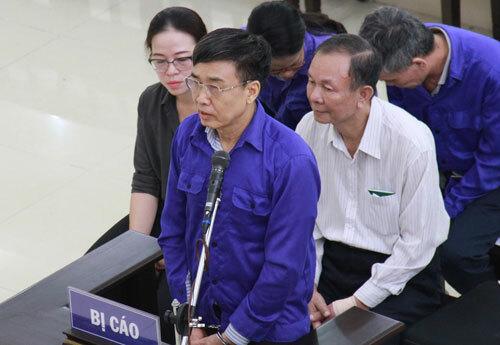 Cựu tổng giám đốc Hồng (đứng) và Ban (áo trắng, ngồi phía sau) trong phần thẩm vấn.