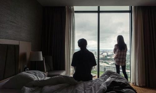 Kim Ye-na (trái) và Lee Jin-hui nhìn ra bên ngoài từ căn phòng khách sạn ở Vientiane, Lào, ngày 22/8. Ảnh: NYTimes.