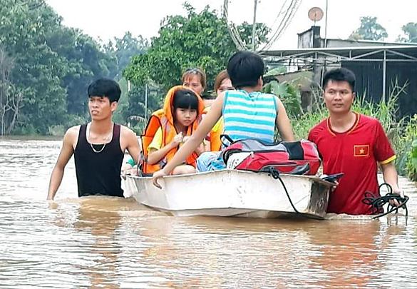 Người dân tại xã Bắc Sơndùng thuyền di dời các em nhỏ đến nơi an toàn. Ảnh:Thái Hà.