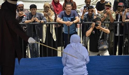 Người dân chứng kiến cảnh một phụ nữ (áo trắng) bị cảnh sát Hồi giáo phạt roi nơi công cộng ở Banda Aceh, tỉnh Aceh hôm nay. Ảnh: AFP.