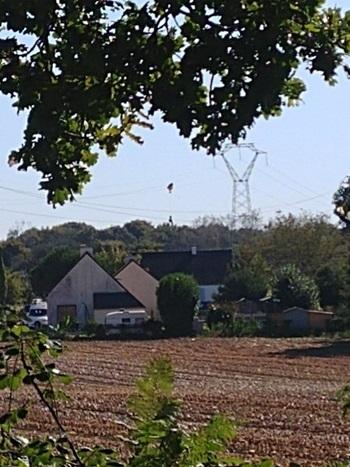 Phi công Bỉ và chiếc dù bị vướng trên dây điện cao thế sau sự cố tiêm kích F-16 gặp nạn ở miền tây nước Pháp hôm nay. Ảnh: Télégramme.