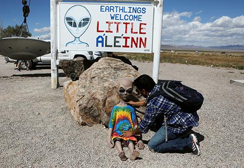 Một người đặt búp bê người ngoài hành tinh bên ngoài Little ALeInn, nhà nghỉ kiêm nhà hàng duy nhất ở Rachel, bang Nevada hôm 19/9. Ảnh: Reuters