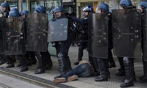 Cánh sát chống bạo động đứng cạnh một người bị thương nằm dưới đất trong cuộc biểu tình áo vàng tại Paris hồi tháng 5. Ảnh: AFP.