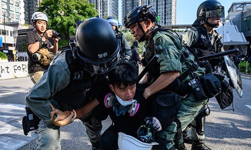 Cảnh sát chống bạo động Hong Kong bắt một người biểu tình tại Tuen Mun chiều 21/9. Ảnh: AFP.