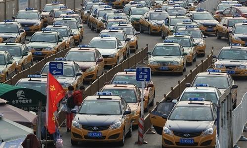 Taxi chờ khách trước nhà ga Bắc Kinh hôm 15/7. Ảnh: Reuters.