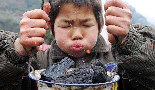 Một em bé ở vùng nông thôn Trung Quốccố giữ ấm bằng cách thổi than trong bếp lò cầm tay hồi tháng 12/2017. Ảnh: Xinhua.