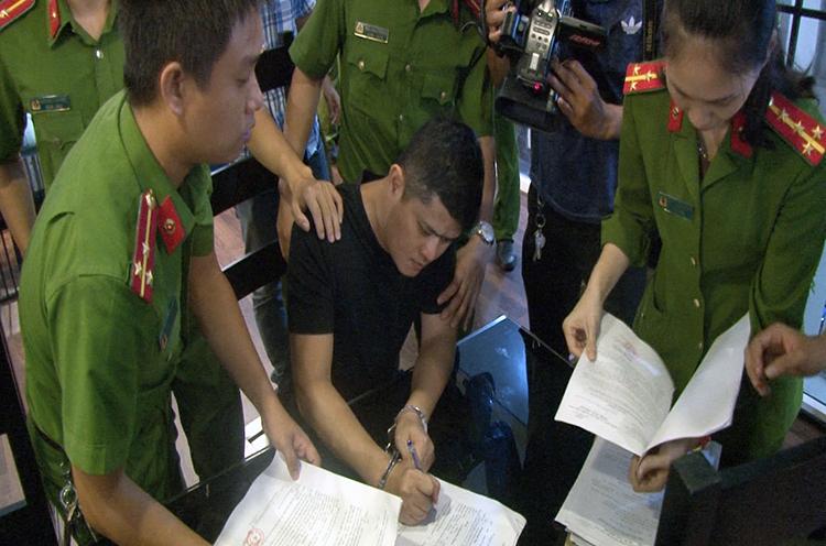 Lê Quang Huy Phương (áo đen) ký vào biên bản khám nhà. Ảnh: Võ Thạnh.