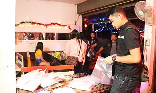 Cảnh sát Thái Lan thu thập bằng chứng và nói chuyện với cácnữ tiếp viên trong cuộc đột kích vào một quán karaoke ở Chiang Mai ngày 5/9. Ảnh: TITAC.