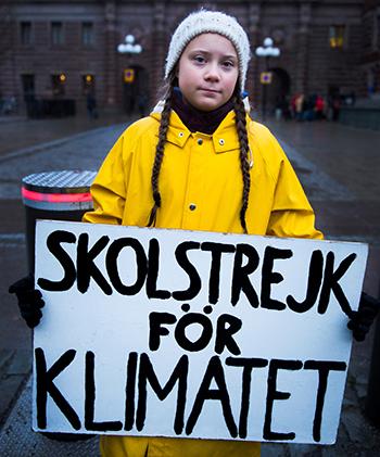 Thunberg cầm biểu ngữ Nghỉ học vì môi trườngbên ngoài quốc hội Thụy Điển tháng 11/2018. Ảnh: Reuters
