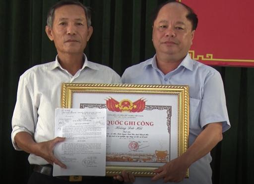 Thừa ủy quyền của Thủ tướng Chính phủ, ông Lê Thế Kỳ (bên phải), Phó chủ tịch UBND huyện Tĩnh Gia trao bằng Tổ quốc ghi công cho thân nhân liệt sĩ Hoàng Đức Hải. Ảnh: Lam Sơn.
