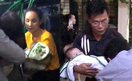 Phó chánh án Nam (bên phải) bế đứa bé xuống taxi. Ảnh: Cắt từ clip.