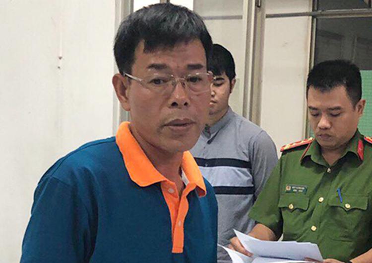 Ông Nguyễn Hải Nam nghe đọc lệnh bắt tạm giam. Ảnh: Công an cung cấp.