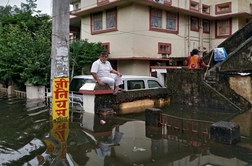Người đàn ông ngồi đợi giải cứu khỏi nước lũ ở Patna, bang Bihar, Ấn Độ ngày 1/10. Ảnh: Reuters.