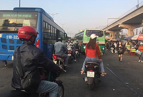 Hai chiếc xe buýt thi nhau ra vào, người đi xe máy rất vất vả. Ảnh: Phan Vĩnh Long