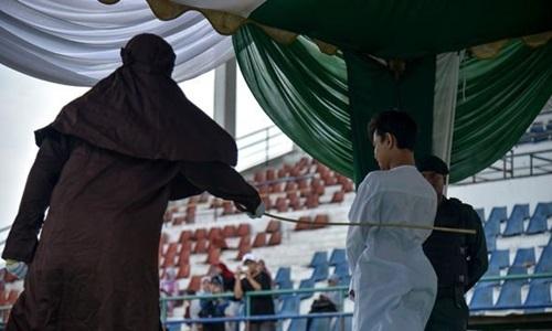 Một người đàn ông Indonesia quan hệ trước hôn nhânbị đánh 100 roi tại sân vận độngLhokseumawe, tỉnh Aceh, ngày 31/7. Ảnh: AFP.