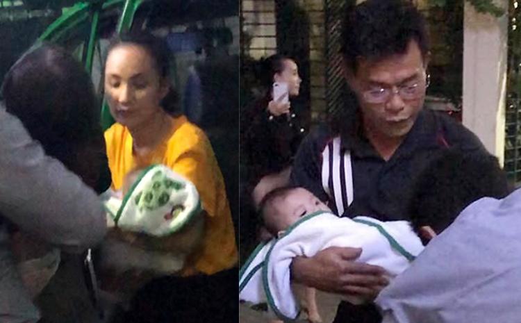 Thẩm phán Nam (phải) và Tâm (áo vàng) bế con chị Thảo. Ảnh cắt từ video.