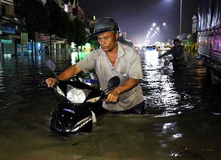 Nước ngập đến yên xe trên quốc lộ 51 qua phường Long Bình Tân, TP Biên Hoà. Ảnh: Phước Tuấn.