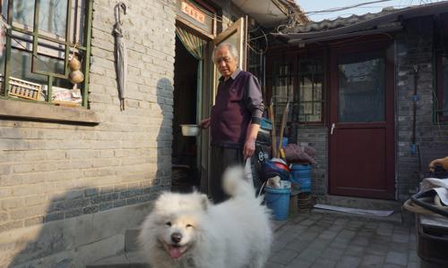 Ông Zhou cùng chó cưng bên ngoài căn nhà ở hẻm Yuer, Bắc Kinh, Trung Quốc. Ảnh: Guardian.