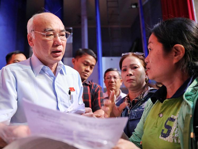 Ông Phan Nguyễn Như Khuê (trái) nhận đơn khiếu nại của cử tri sau buổi làm việc. Ảnh: Hữu Khoa.