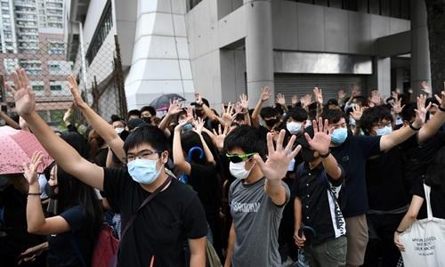 Người biểu tình Hong Kong tập trung bên ngoài tòa án quận phía đông trong phiên xét xử những người đầu tiên vi phạm luật cấm đeo khẩu trang hôm 7/10. Ảnh: AFP.