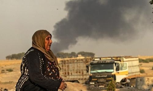 Một phụ nữ đi trên đường khi đám khói từ cuộc tấn côngcủa Thổ Nhĩ Kỳ bốc lên tại Ras al Ain, Syria ngày 9/10. Ảnh: AFP.