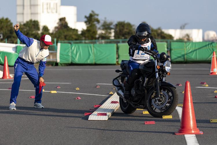 Phần thi thăng bằng trên ván hẹp với mô tô.