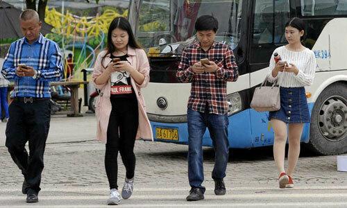 Người đi bộ xem điện thoại khi sang đường ở Trung Quốc. Ảnh: Alamy
