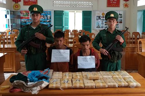 Hai thanh niên người Lào cùng tang vật vụ án. Ảnh: Đức Trí