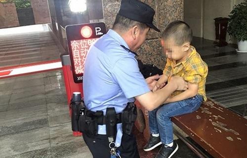 Cảnh sát tới đón cậu bé 4 tuổi ở một bãi đỗ xe tạithành phố Đại Túc, tỉnh Trùng Khánh, Trung Quốc, hôm 7/10. Ảnh: SCMP.