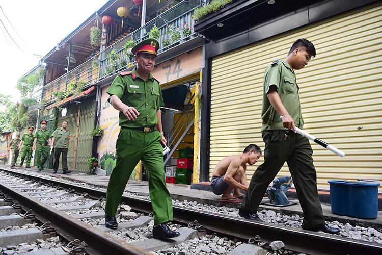 Công an quận Hoàn Kiếm đi nhắc nhở các chủ quán cam kết không bày bàn ghế ra đường tàu. Ảnh: Giang Huy.