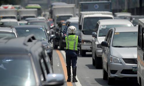 Cảnh sát điều khiển các phương tiện tại một trục đường ở Manila. Ảnh: AFP