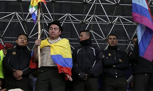 Một cảnh sát Ecuador bị bắt khoác cờ và giơ biểu ngữ trên một sân khấu ở thủ đô Quito ngày 10/10. Ảnh: AP.