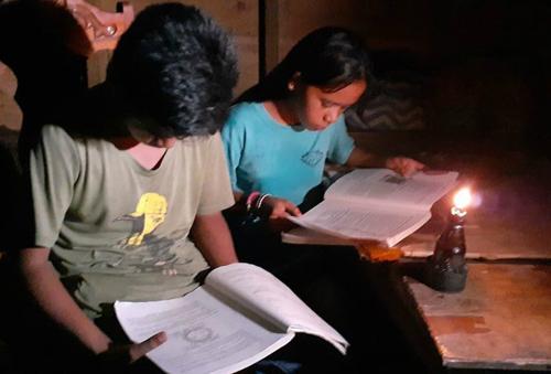 Jerom Felipe và em gái ngồi học bên cạnh chiếc đèn dầu. Ảnh: ABS-CBN News.
