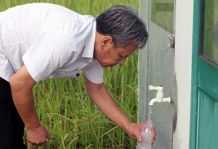 Cán bộ Trung tâm kiểm soát bệnh tật thành phố lấy mẫu nước tại Nhà máy nước sạch sông Đà chiều 11/10. Ảnh: Võ Hải.