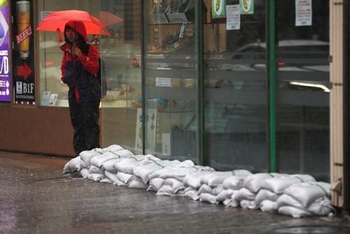 Người phụ nữ che ô dưới cơn mưa nặng hạt bên cạnh một cửa hàng được chất đầy bao cát ở Tokyo hôm nay trước khi bão Hagibis đổ bộ. Ảnh: Reuters.