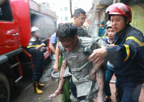 Trung uý Hoàng cõng Giang đã ngất xỉu trong đám cháy hôm 10/9 ở phố Núi Trúc. Ảnh: P.X.