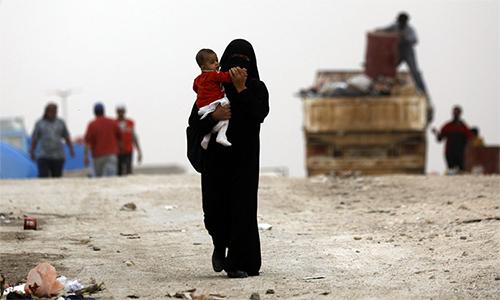 Một phụ nữ bế con tại trại tị nạn Ain Issa, Syria. Ảnh: AFP.