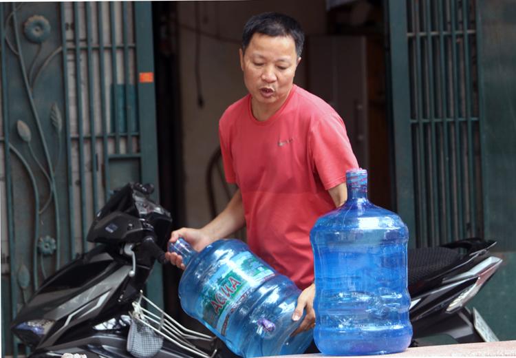 Nước đóng bình được chuyển đến nhà người dân ở Khương Đình, Thanh Xuân. Ảnh: Võ Hải.