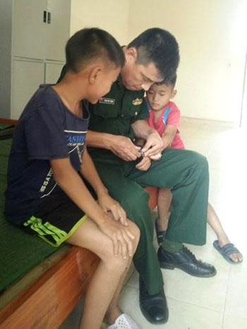 Thượng tá Mạnh cắt móng tay cho hai anh em Khoa và Xuyên. Ảnh: P.X.